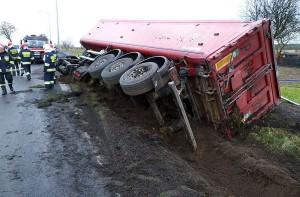 Naczepa przewróciła się na bok, a ładunek wysypał częściowo do rowu, a częściowo na jezdnie.