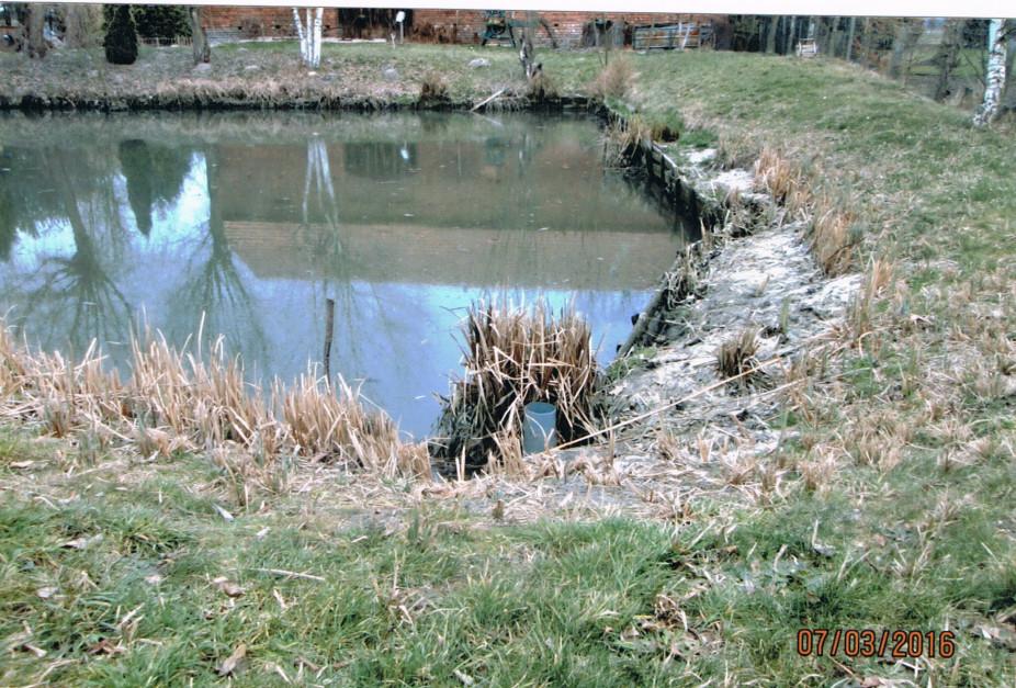 Zbiornik, na pierwszym planie pozostałość urządzenia do piętrzenia wody