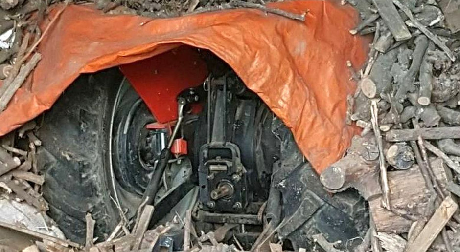 Skradziony ciągnik ukryty w stercie drewna