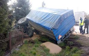 Traktor z przyczepą po zderzeniu wywrócił się na ogrodzeniu posesji. Z przyczepy wysypało się ziarno