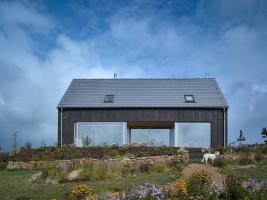 Na pokrycie dachu zdecydowano się zastosować tradycyjne dachówki ceramiczne, z nowoczesną szarą glazurą i prostym kształtem. Dzięki temu zabiegowi dom wyróżnia prosta i wyrazista forma przyozdobiona modnymi szarymi i ciemnymi kolorami oraz wielkoformatowymi przeszkleniami
