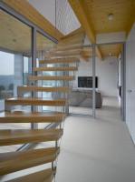 Na górne piętro prowadzą jednopoziomowe schody zlokalizowane obok ogrodu zimowego
