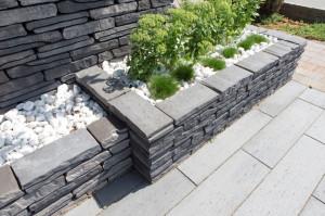 Ważnym elementem kompozycyjnym mogą być także murki. Można z nich budować murki ozdobne oraz oporowe, które pozwolą podzielić ogród na sekcje lub wyróżnić jakąś strefę. Można z niego wznieść również obudowę dla ogrodowej fontanny lub oczka wodnego, fot. Polbruk