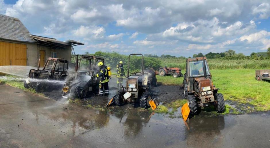 Cztery spalone ciągniki, auto i stodoła