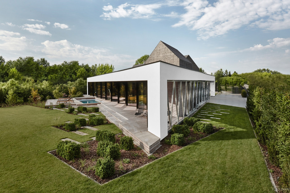 Dom z Trójkątów to parterowy budynek podkreślony drewnem. Białe ramy, otaczające dom na krawędziach elewacji, zostały zastosowane jako dopełnienie bryły. Projekt: 81.waw.pl, Foto. Bartek Zaranek