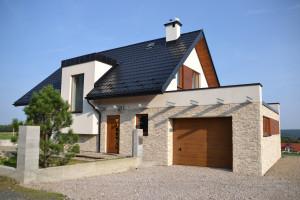 Dom ma powierzchnię użytkową 114 mkw. oraz garaż o powierzchni ponad 50 mkw. Na parterze znajduje się część dzienna z salonem połączonym z kuchnią, do tego mały pokój wykorzystywany jako miejsce pracy lub sypialnia dla gości i mała łazienka.