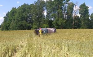 Bmw po zderzeniu z traktorem dachowało na polu, Foto: Policja