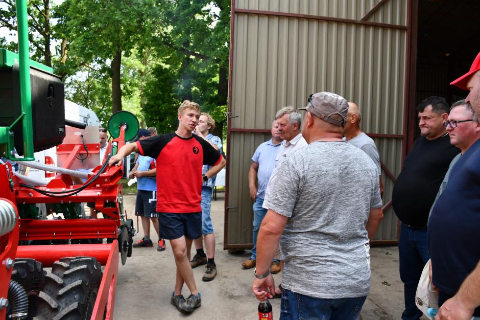 Krystian Nowak, syn właściciela gospodarstwa, prezentuje rolnikom siewnik do uprawy pasowej, który został użyty w doświadczeniu, fot. HJ