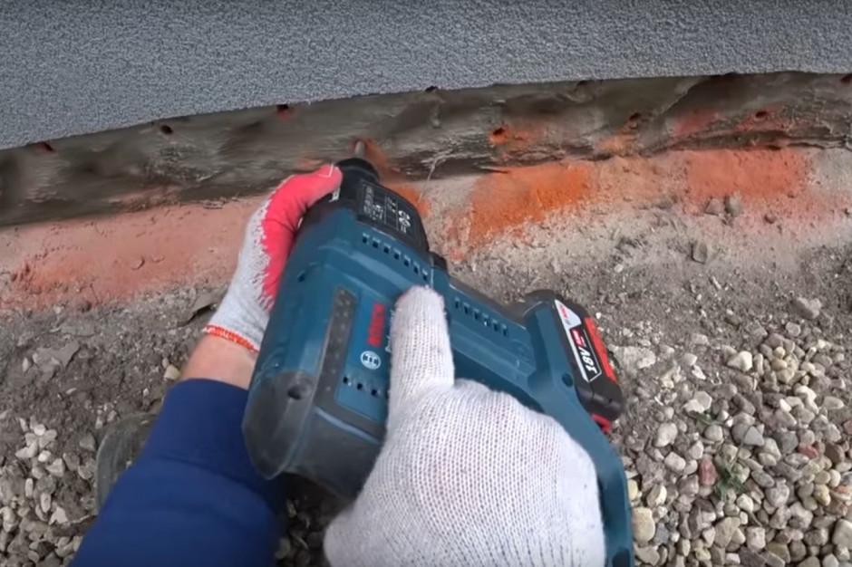 Przy użyciu wiertarki, należy wywiercić otwory iniekcyjne. Powinny mieć średnicę 10-14 mm i sięgać na głębokość ok. ¾ ściany. Linia otworów powinna się znajdować na wysokości co najmniej 10 cm nad uszkodzoną izolacją poziomą. Odległość skrajnych otworów od krawędzi murów powinna wynosić 5-10 cm. Foto. Materiały Prasowe Firmy